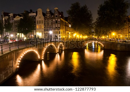 Amsterdam canal at night with lights on the bridges