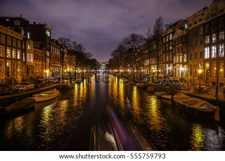 AMSTERDAM, NETHERLANDS - JANUARY 12, 2017: Beautiful night city canals of Amsterdam with moving passanger boat. January 12, 2017 in Amsterdam - Netherland.