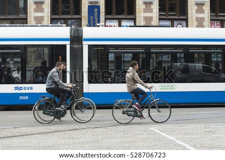 AMSTERDAM, NETHERLANDS - JULY 8, 2015: Three young men on bicycles pass next to a tram two units.