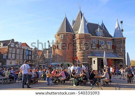 "AMSTERDAM, NETHERLANDS - MAY 5, 2016:People in outdoor cafe on Nieuwmarkt (New Market) square in center of Amsterdam, Netherlands.The Waag (""weigh house"") is 15th-century building on Nieuwmarkt square"
