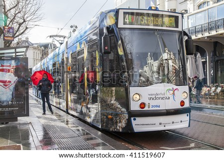 AMSTERDAM, NETHERLANDS on MARCH 27, 2016. Typical urban view in the spring afternoon. The tram moves down the street