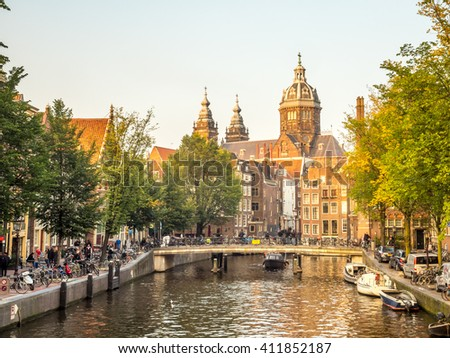 AMSTERDAM - OCTOBER 4: Saint Nicholas church is landmark of Amsterdam, unique with city scene along canal in evening natural light, was taken on October 4, 2015, Netherlands.