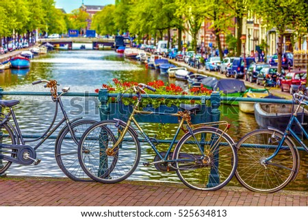 Amsterdam, The Netherlands - August 26. 2011.: Bicycles and flowers on a small bridge over the canal in Amsterdam. Flowers blossom and bicycles on a small bridge in Amsterdam, HDR Image.
