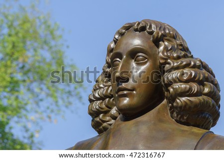 Amsterdam, the Netherlands - August 16, 2016: The famous philosopher Baruch Spinoza has his statue near the Bijvoetbrug. Detail of bronze shows serious looking man with long curly hair.