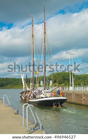 AMSTERDAM, THE NETHERLANDS - SEP 11, 2016: Sailing boat leaves Oranje locks on the city's IJ river. The locks are built in 1872