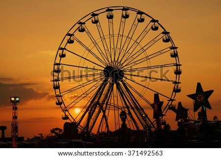 amusement park in silhouette sunset,