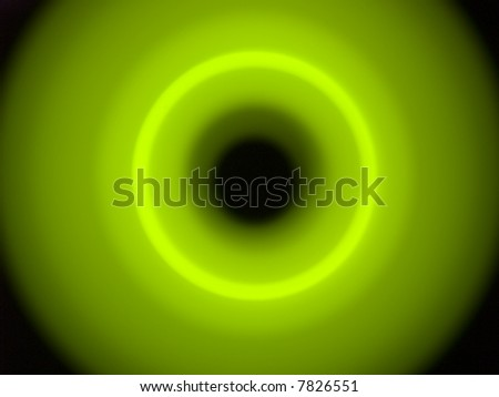 An abstract green light ring on a dark background. The light is intentionally out of focus and blurred for effect.