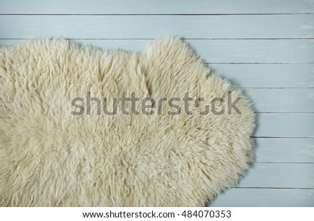 an aerial view of a cozy white sheepskin rug on a painted wooden floor background
