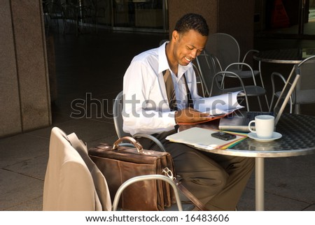 An African American businessman smiles as he is please with the information he is reading.
