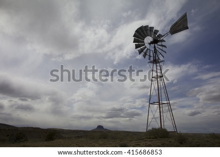 An afternoon thunderstorm seems to be rolling in, seen behind the silhouette of an antique windmill, with Cabezon Peak in the distance on the desert plains of New Mexico.