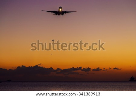 An airplane approaching the runway for landing during the sunset