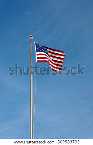 An American Flag flying in the air up a pole
