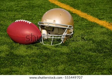 An American football helmet and ball on a field by the goal line