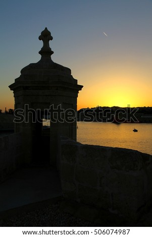 An ancient lookout post or Gardjola keeps guard on the Grand Harbour as night falls