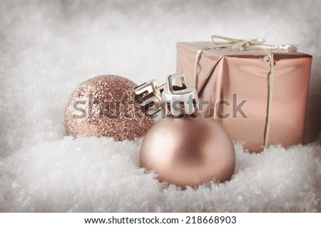 An Arrangement Of Pale Peach Pink Christmas Decorations Sinking Into Soft,  White Artificial Snow.