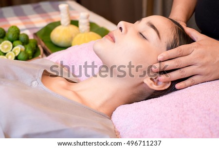 An attractive Caucasian woman getting massaged by a therapist. woman getting head and neck massage by therapist