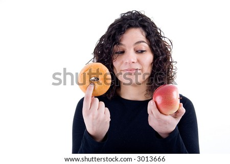 an attractive fit girl weighs her options of weather to eat donut or an apple