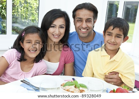 An attractive happy, smiling Asian Indian family of mother, father, son and daughter eating healthy food at a dining table.