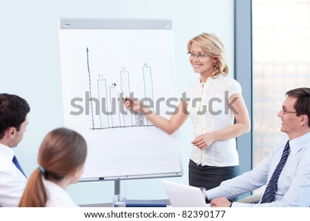 An attractive woman tells a presentation at the office