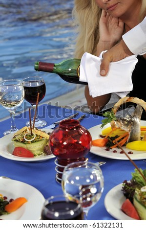 An attractive young woman having wine by the pool - a series of RESTAURANT images.