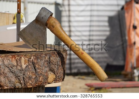 An axe and a knife stuck in a log and expect of their work.