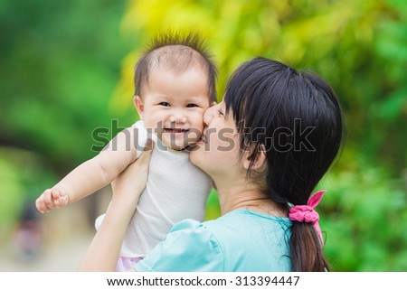 An emotional portrait of happy people : mother kissing her 9 months baby in the garden.