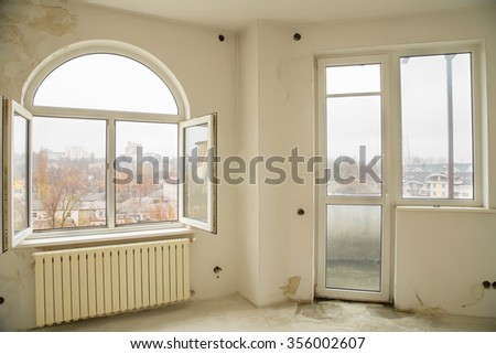 An empty interior of a nearly finished apartment with white walls and big windows