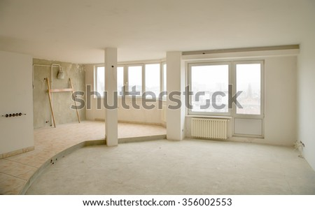 An empty interior of a newly built apartment with white walls and big windows