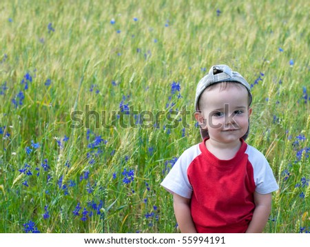 An expressive boy is standing in the summer meadow