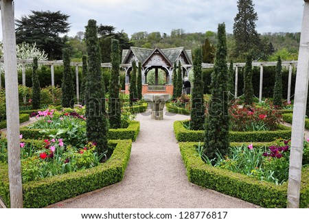 An Formal Landscape garden with Box Hedging and colorful flowerbeds and Topiary