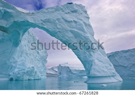 an ice arch carved by the wind in a giant iceberg, greenland