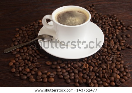 An image of a cup of coffee and coffee beans