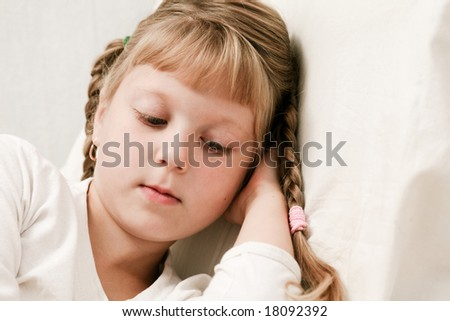 An image of ill girl on a bed under cover