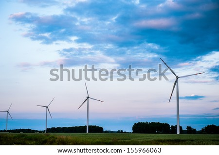 An image of wind turbines at sunset