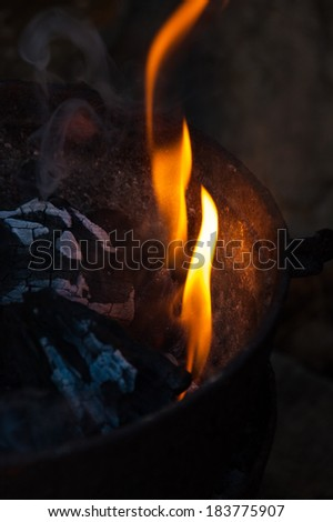 An iron bucket full of charcoal dark with some flames ember and ash