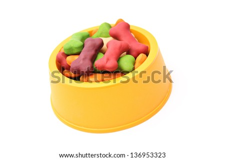 An isolated dog bowl with dog biscuits on a white background.