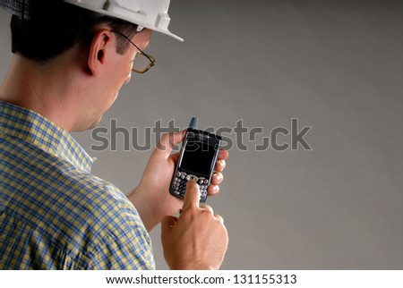 An Male Architect Wearing Glasses Using A PDA Cellphone Isolated On A Grey Background, With Copyspace