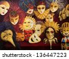 An oil painting on canvas of a colorful ornate traditional venetian masks on display, over a dark red curtain. - stock photo