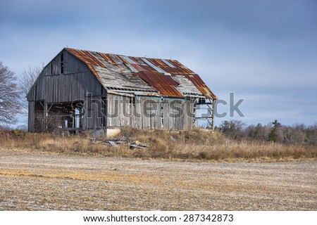 An old barn with weathered gray boards and a rusty roof sits in a farm field.