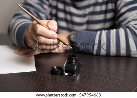 An old man is dressed in striped sweater going to write something in a blank