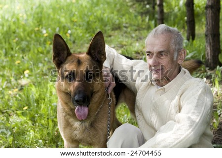 An old man who is sitting on nature with his dog.
