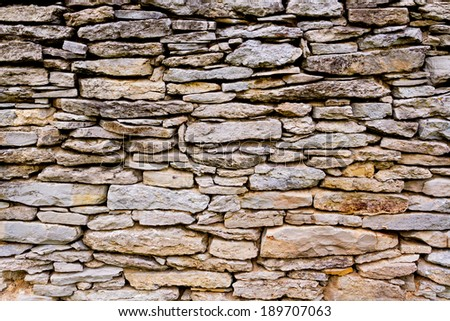 An old, weathered wall is composed of many textured limestone rocks.