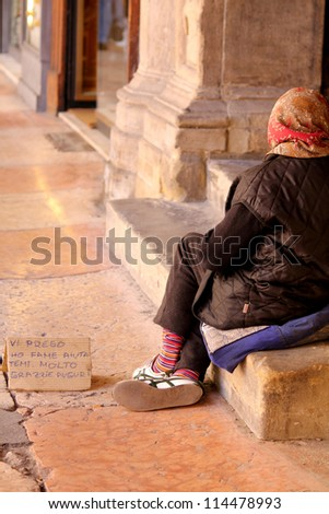 an old woman in the streets of Italy begging for some change