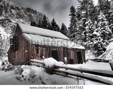An old wooden barn in a snow storm.