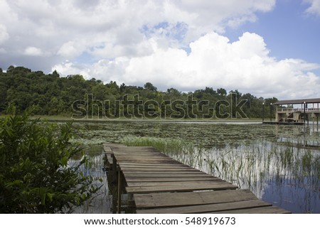 An old wooden bridge port beside lake tasik chini cloudy day