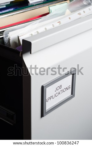 An open filing drawer, labeled 'Job Applications' and filled messily with hanging files, folders, plastic wallets and papers.  Portrait orientation.