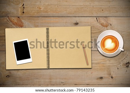 An open notebook and instant photo with cup of coffee