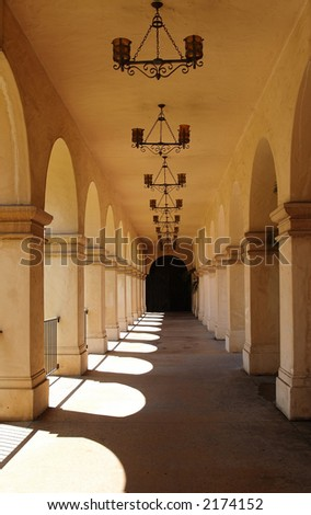 An outdoor breezeway lined with arches leading to beautiful gardens in Southern California.  Done with a heavy spanish influence