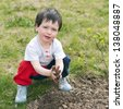 An outdoor portrait of a cute child playing with earth soil in a garden. - stock photo