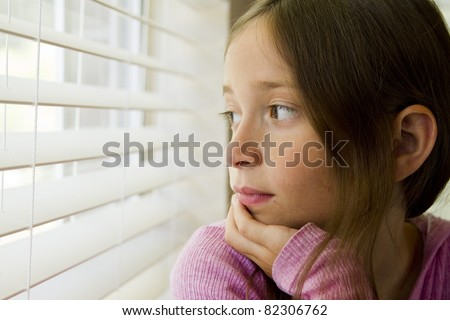 An unsmiling young girl gazes through window blinds.